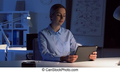 businesswoman having video call at night office