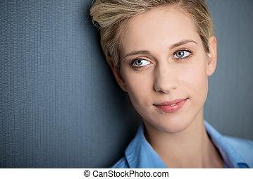 businesswoman, het glimlachen, terwijl, kijken weg, tegen, blauwe muur