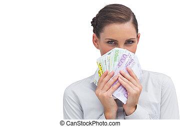 Businesswoman hiding behind money