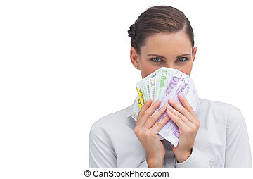 Businesswoman hiding behind money