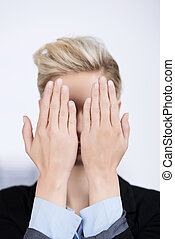 Businesswoman Hiding Face With Hands In Office