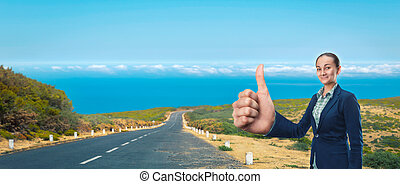 Businesswoman hitching a lift on the road near the sea
