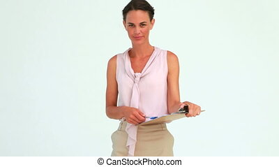 Businesswoman holding a clipboard putting her pen in her mouth