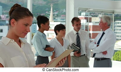 Businesswoman holding a clipboard with colleagues in background