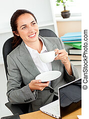 Businesswoman holding a cup of coffee in front of her laptop sitting at her desk in her office