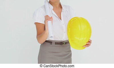 Businesswoman holding a hard hat and blueprints