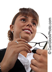 Businesswoman holding a pair of glasses