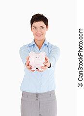 Businesswoman holding a piggy bank