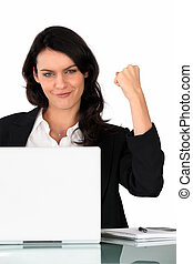 Businesswoman holding a triumphant fist in the air