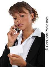 businesswoman holding a visit card and talking on her cell