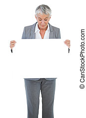 Businesswoman holding and looking at blank sign on white background