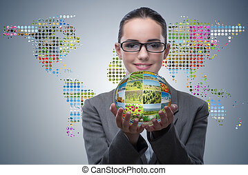 Businesswoman holding ball made of nature photos