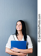 Businesswoman Holding Binder Against Blue Wall - Thoughtful...