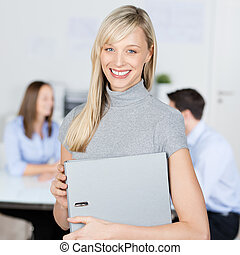 Businesswoman Holding Binder With Coworkers In Background