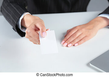 Businesswoman holding blank visit card ,sitting on the desk