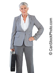 Businesswoman holding briefcase and putting her hand on hip