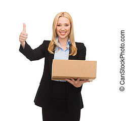 businesswoman holding cardboard box and showing thumbs up