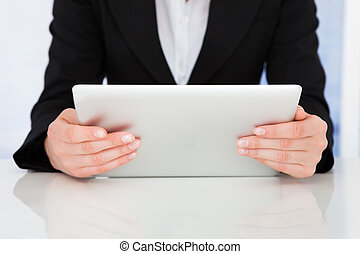 Businesswoman Holding Digital Tablet At Desk