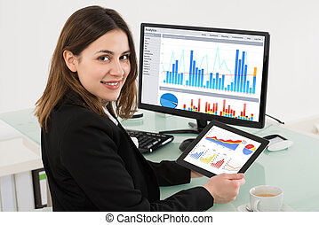 Businesswoman Holding Digital Tablet While Working In Office