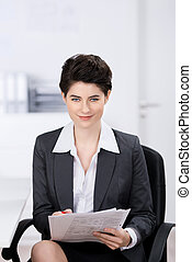 Businesswoman Holding Documents At Desk