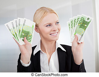 Businesswoman holding euro currency notes
