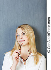 Businesswoman Holding Eyeglasses While Looking Away