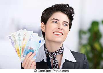 Businesswoman Holding Fan Of Euro Notes In Office