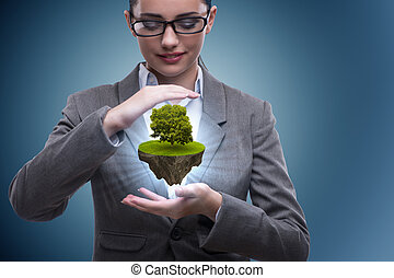 Businesswoman holding floating island with tree