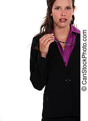 Businesswoman holding glasses to mouth