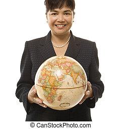 Businesswoman holding globe.