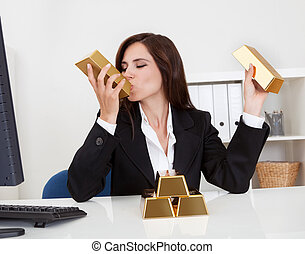 Portrait of a beautiful young businesswoman holding gold bar at office desk