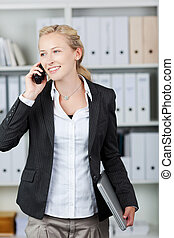 Businesswoman Holding Laptop While Using Mobile Phone -...