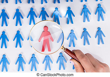 Businesswoman Holding Magnifying Over Red Human Figure