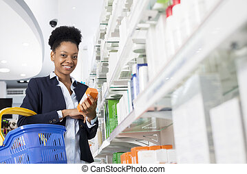 Businesswoman Holding Medicine By Shelves In Pharmacy