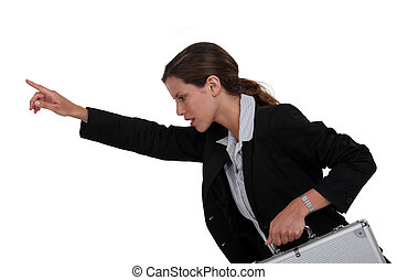Businesswoman holding metal briefcase and pointing