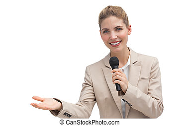 Businesswoman holding microphone and smiling at the camera