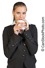 Businesswoman holding mug at her mouth, looking at camera....