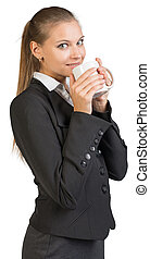Businesswoman holding mug at her mouth, looking at camera,...