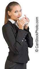Businesswoman holding mug at her mouth, her lips parted,...