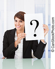 Businesswoman Holding Paper With Question Mark In Front Of Face