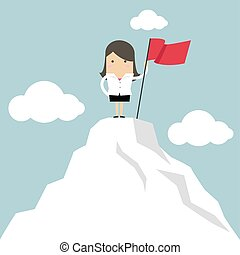 Businesswoman holding red flag on the top of the mountain.