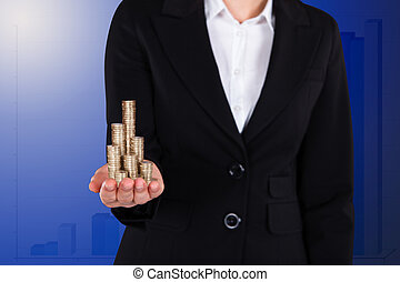 Businesswoman Holding Stacked Coins