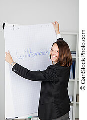 Businesswoman Holding Welcome Sign In Office