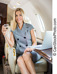Businesswoman Holding Wineglass In Private Jet - Portrait of...