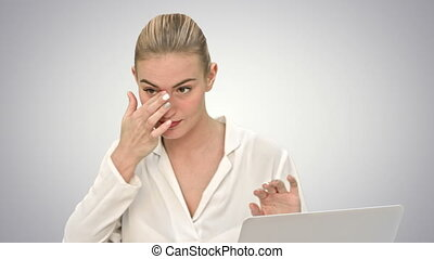 Businesswoman in a good mood dance, sitting on the desk with laptop, and answer a phone call on white background.