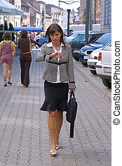 Businesswoman in a hurry - Walking businesswoman while she...