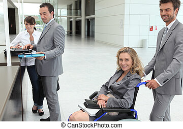 Businesswoman in a wheelchair with colleagues checking in at reception
