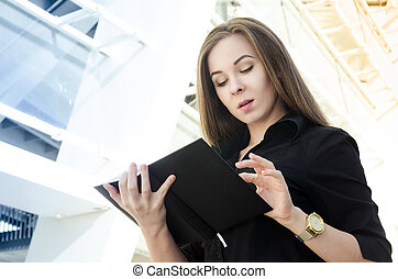 businesswoman in black clothes with long hair flips a black notebook