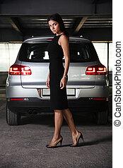 Businesswoman in black dress walking on car parking