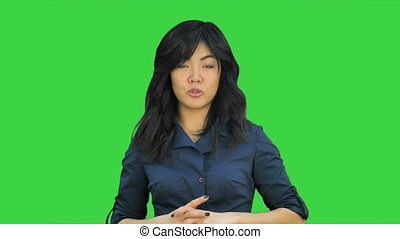 Businesswoman in blue suit smiling looking at camera explaining with gesture on a Green Screen, Chroma Key